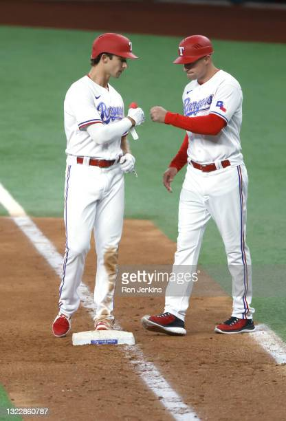 Eli White of the Texas Rangers is congratulated by first base coach Corey Ragsdale after hitting a single against the San Francisco Giants during the...