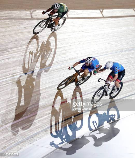 Elia Viviani and Simon Consonni of Italy hand over as Mark Cavendish of Great Britain looks on during Men's Team Elimination race on Day Three of the...