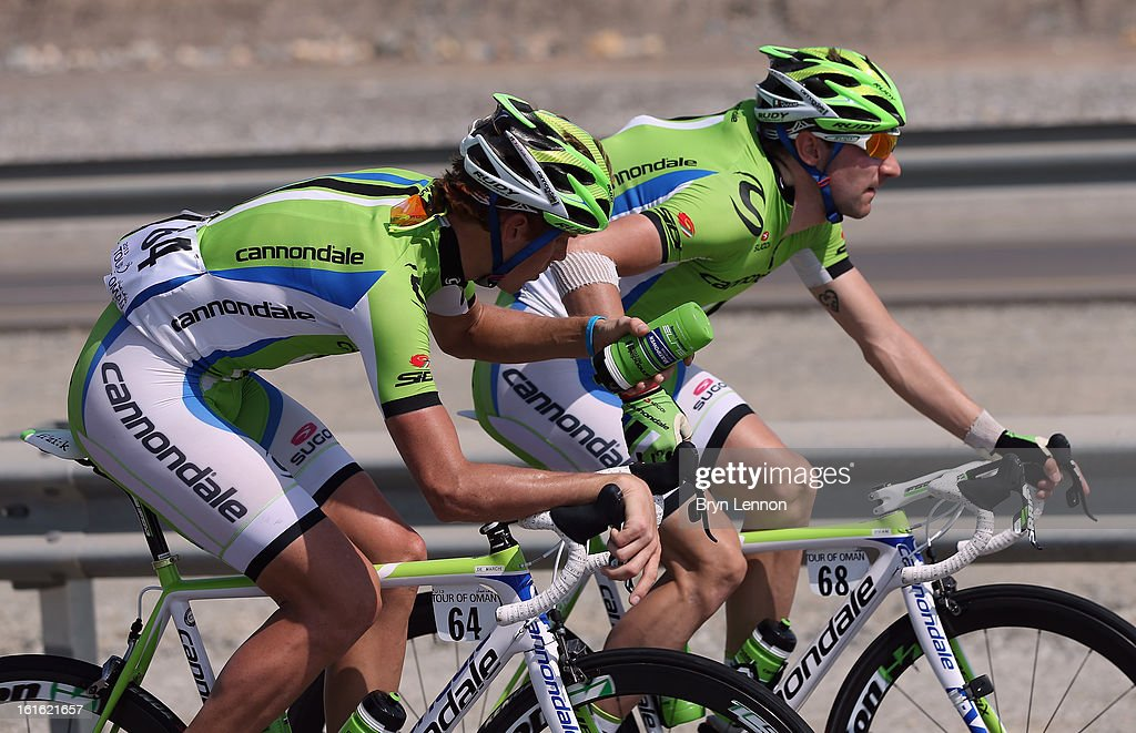 Elia Viviani of Italy and Cannondale passes a water bottle to team mate Alessandro De Marchi of Italy during stage three of the 2013 Tour of Oman from Nakhal Fort to Wadi Dayqah Dam on February 13, 2013 in Wadi Dayqah Dam, Oman.