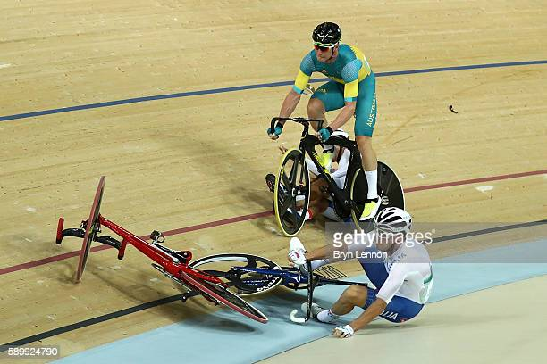Elia Viviani of Italy Glenn O'Shea of Australia and Sanghoon Park of Korea crash during the Cycling Track Men's Omnium Points Race 66 on Day 10 of...