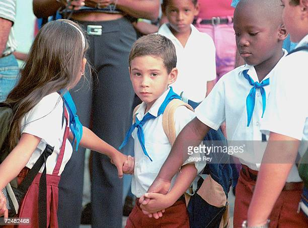 Elian Gonzalez arrives at school with Mayren Rodriguez left and Hanser Munoz September 1 2000 on the first school day in Cardenas Cuba