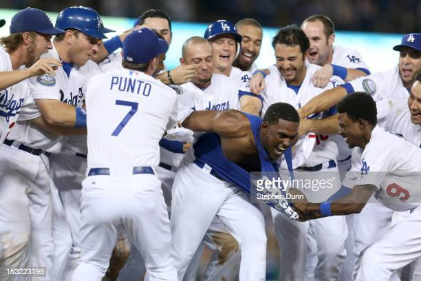 Elian Herrera of the Los Angeles Dodgers has his tee shirt torn off by Dee Gordon as Herrera is mobbed by teammates after his walk off RBI single in...