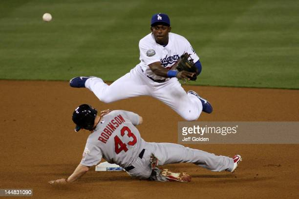 Elian Herrera of the Los Angeles Dodgers leaps over a sliding Shane Robinson of the St Louis Cardinals as he throws to first base to complete a...