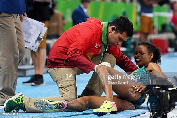 Eliane Martins of Brazil is assisted by a trainer during the Women's Long Jump Qualifying Round on Day 11 of the Rio 2016 Olympic Games at the...