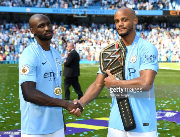 Eliaquim Mangala of Manchester City and Yaya Toure of Manchester City shake hands on the pitch with a WWE belt after the Premier League match between...