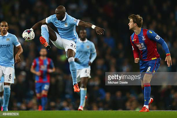 Eliaquim Mangala of Manchester City clears from Patrick Bamford of Crystal Palace during the Capital One Cup fourth round match at the Etihad Stadium...