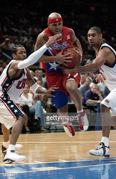 Elias Ayuso of Puerto Rico splits the defense of Allen Iverson and Tim Duncan of the USA during an exhibition game on August 17 2003 at Madison...