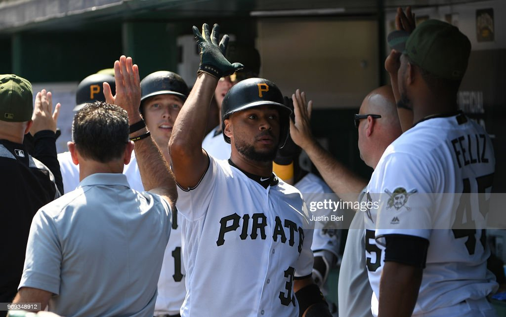 Elias Diaz #32 of the Pittsburgh Pirates is greeted by teammates in the dugout after hitting a three run home run in the eighth inning during the game against the Los Angeles Dodgers at PNC Park on June 7, 2018 in Pittsburgh, Pennsylvania.