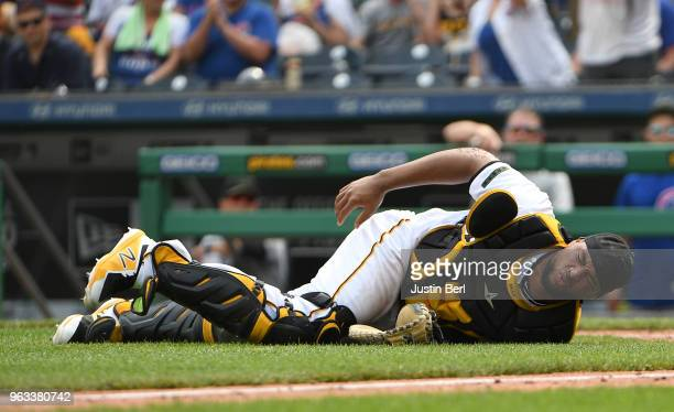 Elias Diaz of the Pittsburgh Pirates lays on the ground after being taken out on a slide by Anthony Rizzo of the Chicago Cubs in the eighth inning...