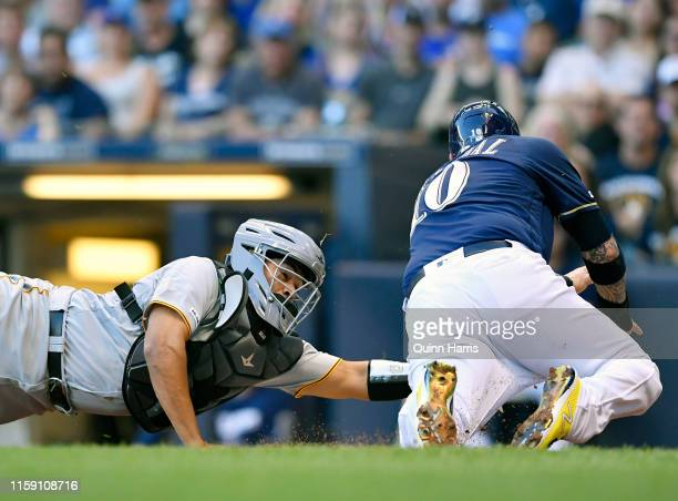Elias Diaz of the Pittsburgh Pirates tags out Yasmani Grandal of the Milwaukee Brewers at home plate in the first inning at Miller Park on June 29...