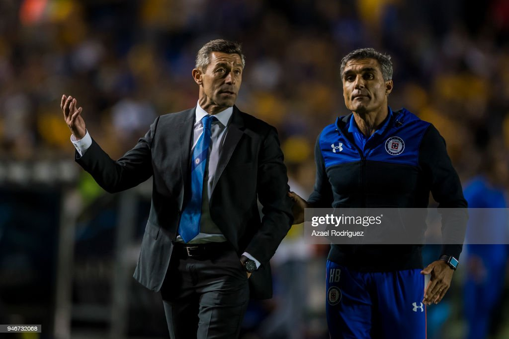 Elias Domingos tries to calm down Pedro Caixinha, coach of Cruz Azul, after he was expeled from the field during the 15th round match between Tigres UANL and Cruz Azul as part of the Torneo Clausura 2018 Liga MX at Universitario Stadium on April 14, 2018 in Monterrey, Mexico.