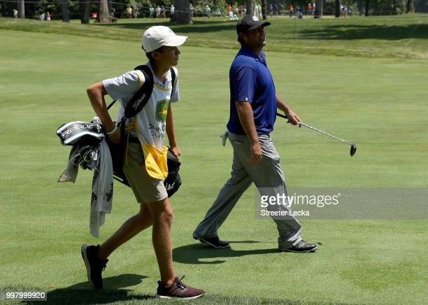 Elias Francque a 17yearold high school student caddies for Steven Bowditch of Australia on the 18th hole during the second round of the John Deere...