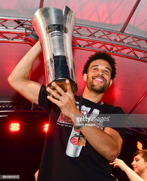 Elias Harris of Brose Bamberg raises the trophy of the German basketball championship at Maxplatz on June 11 2017 in Bamberg Germany
