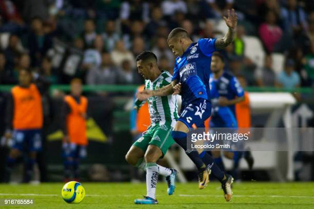 Elias Hernandez of Leon figths the ball with Christian Tabo of Puebla during the 6th round match between Leon and Puebla as part of the Torneo...