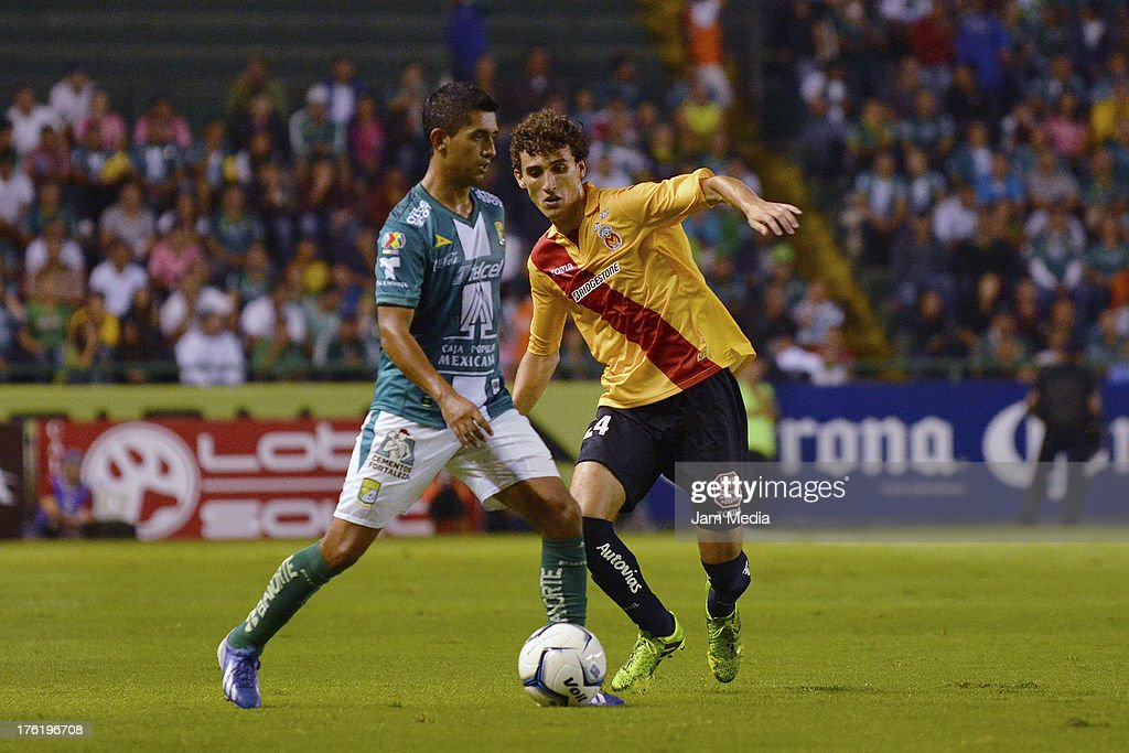 Elias Hernandez (L) of Leon struggles for the ball with Aldo Rodrigo Godinez (R) of Morelia during the Apertura 2013 Liga Bancomer MX at Nou Camp Stadium on August 10, 2013 in Leon, Mexico.