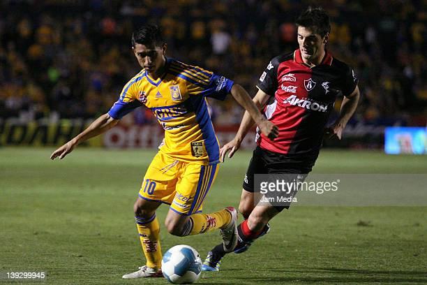 Elias Hernandez of Tigres struggles for the ball with Facundo Erpen of Atlas during a match as part of the Clausura 2012 at Universitario Stadium on...