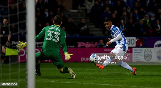 Elias Kachunga of Huddersfield scores the opening goal past Michael McGovern of Norwich during the Sky Bet Championship match between Huddersfield...