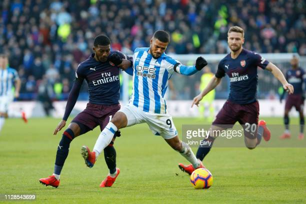Elias Kachunga of Huddersfield Town battles with Ainsley MaitlandNiles during the Premier League match between Huddersfield Town and Arsenal FC at...