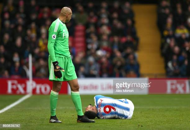 Elias Kachunga of Huddersfield Town goes down injured as Heurelho Gomes of Watford looks on during the Premier League match between Watford and...