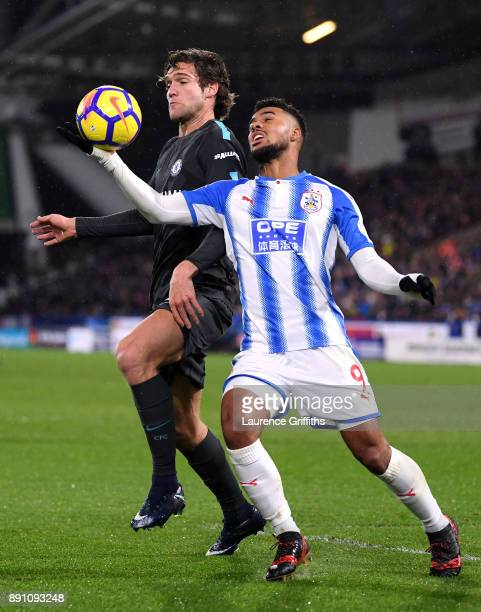 Elias Kachunga of Huddersfield Town handles the ball under pressure from Marcos Alonso of Chelsea during the Premier League match between...