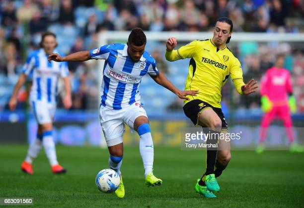 Elias Kachunga of Huddersfield Town is tackled by Jackson Irvine of Burton Albion during the Sky Bet Championship match between Huddersfield Town and...
