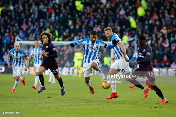 Elias Kachunga of Huddersfield Town looks to burst between Ainsley MaitlandNiles and Matteo Guendouzi of Arsenal during the Premier League match...