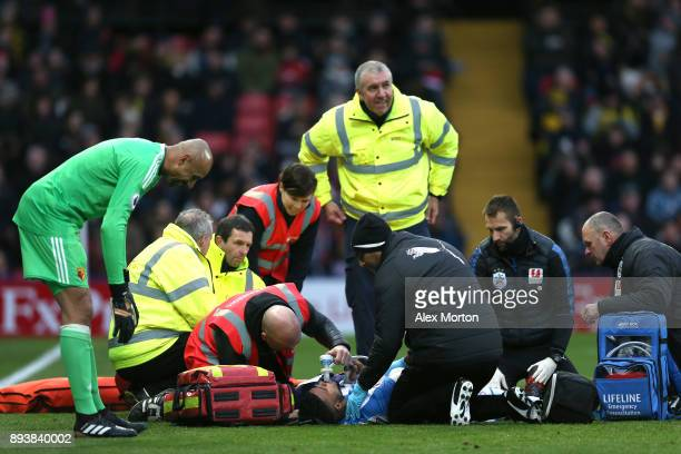 Elias Kachunga of Huddersfield Town receives treatment from the medical team during the Premier League match between Watford and Huddersfield Town at...