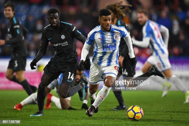 Elias Kachunga of Huddersfield Town runs with the ball under pressure from Tiemoue Bakayoko of Chelsea during the Premier League match between...