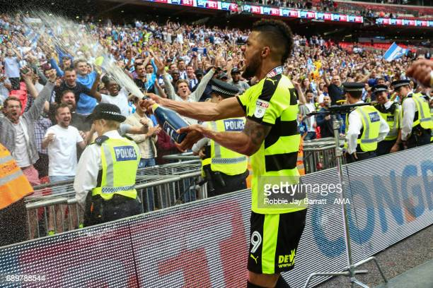 Elias Kachunga of Huddersfield Town sprays champagne at the fans during the Sky Bet Championship Play Off Final match between Reading and...