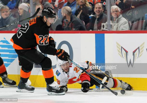 Elias Lindholm of the Calgary Flames falls to the ice while battling for the loose puck along the boards with Dale Weise of the Philadelphia Flyers...