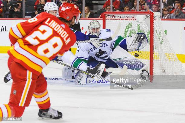 Elias Lindholm of the Calgary Flames scores the gamewining goal against Jacob Markstrom of the Vancouver Canucks during an NHL game at Scotiabank...