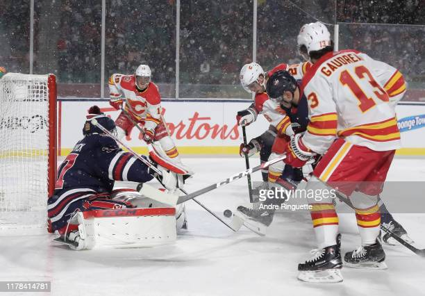 Elias Lindholm of the Calgary Flames shoots the puck past Connor Hellebuyck of the Winnipeg Jets to score a second period goal during the 2019 Tim...