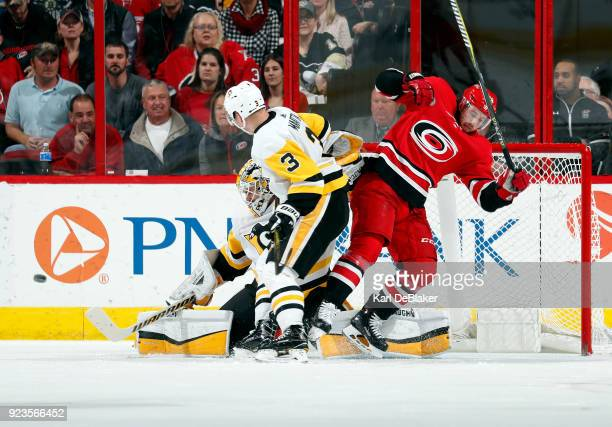Elias Lindholm of the Carolina Hurricanes and Oli Maatta of the Pittsburgh Penguins jostle for position in the crease as Matt Murray defelcts a shot...