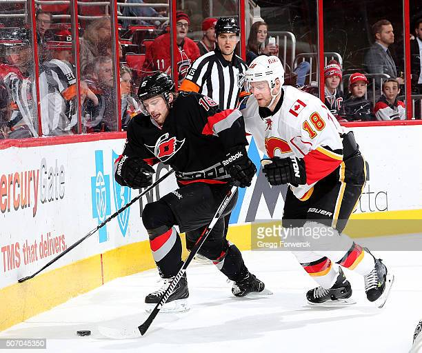 Elias Lindholm of the Carolina Hurricanes battles for a loose puck with Matt Stajan of the Calgary Flames during an NHL game at PNC Arena on January...