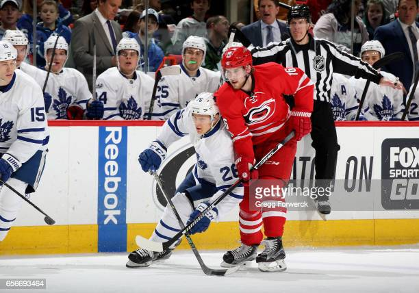 Elias Lindholm of the Carolina Hurricanes battles for position on the ice with Nikita Soshnikov of the Toronto Maple Leafs during an NHL game on...