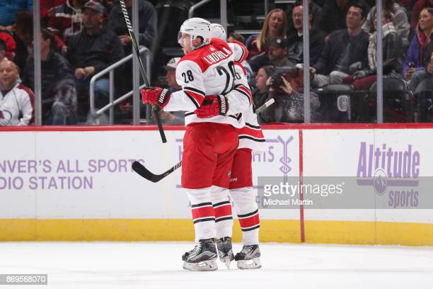 Elias Lindholm of the Carolina Hurricanes celebrates a goal against the Colorado Avalanche with teammate Sebastian Aho at the Pepsi Center on...