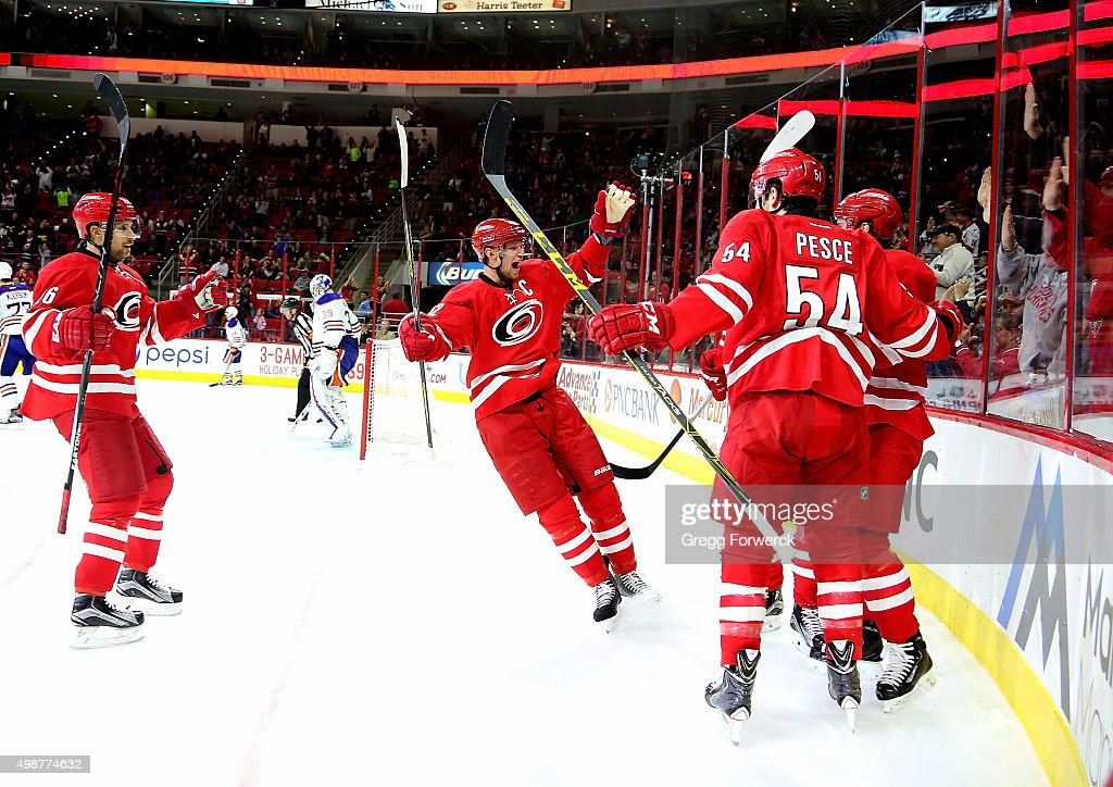 Elias Lindholm #16 of the Carolina Hurricanes celebrates his second period goal with teammates Eric Staal #12, Brett Pesce #54, and John-Michael Liles #26 during a NHL game against the Edmonton Oilers at PNC Arena on November 25, 2015 in Raleigh, North Carolina.