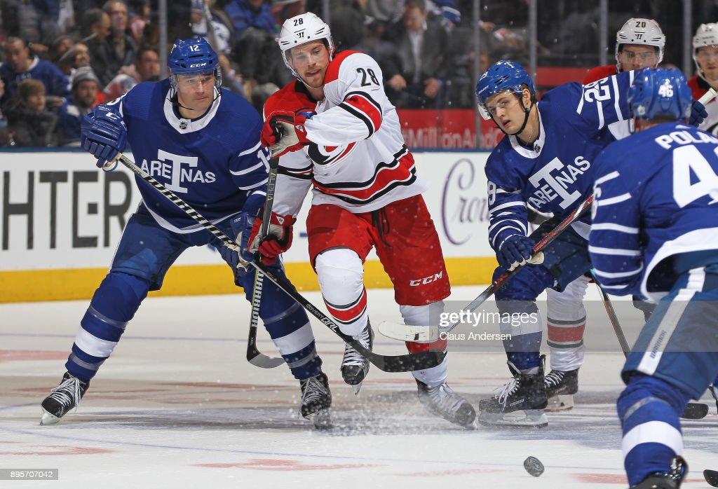 Elias Lindholm #28 of the Carolina Hurricanes skates against Patrick Marleau #12 of the Toronto Maple Leafs during an NHL game at the Air Canada Centre on December 19, 2017 in Toronto, Ontario, Canada. The Maple Leafs defeated the Hurricanes 8-1.