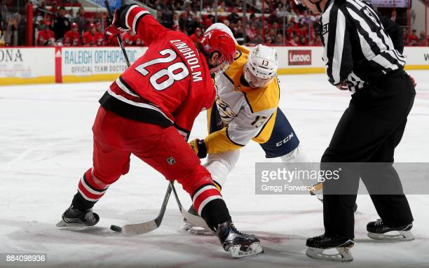 Elias Lindholm of the Carolina Hurricanes wins a faceoff against Nick Bonino of the Nashville Predators during an NHL game on November 26 2017 at PNC...