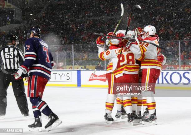 Elias Lindholm, Sean Monahan, Mark Giordano, Matthew Tkachuk and Johnny Gaudreau of the Calgary Flames celebrate Lindholm's goal as Dmitry Kulikov of...