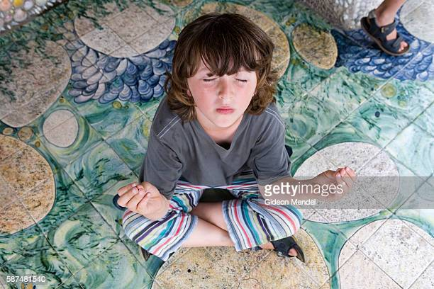 Elias Mendel strikes a meditation pose in one of the colourfully decorated shelters in Tresco Abbey Garden, on Tresco island in the Scilly Isles....