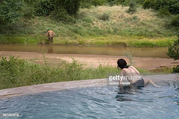 Elias Mendel watches an elephant drinking from the Luvuvhu River as he climbs out of one of the beautifully situated swimming pools at Pafuri Lodge...