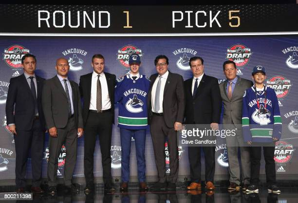 Elias Pettersson fifth overall pick of the Vancouver Canucks poses for a photo onstage with the Canucks draft team during Round One of the 2017 NHL...