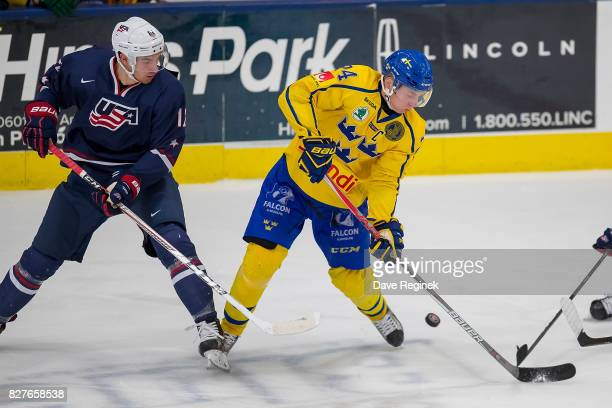Elias Pettersson of Sweden battles for the puck with Tim Gettinger of the USA during a World Jr Summer Showcase game at USA Hockey Arena on August 2...