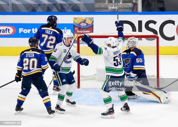 Elias Pettersson of the Vancouver Canucks celebrates his power-play goal at 5:36 of the third period against the St. Louis Blues and is joined by Bo...