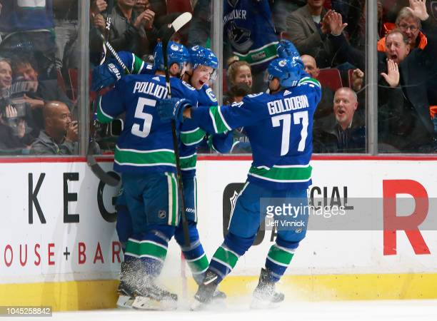 Elias Pettersson of the Vancouver Canucks is congratulated by teammates after scoring his first NHL goal during their game against the Calgary Flames...
