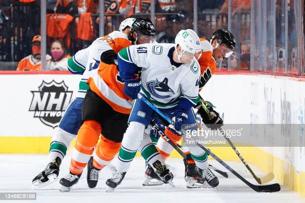 Elias Pettersson of the Vancouver Canucks is defended by Nate Thompson and Nick Seeler of the Philadelphia Flyers during the second period at Wells...