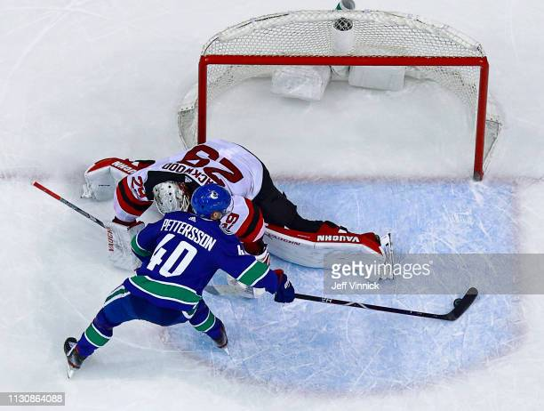 Elias Pettersson of the Vancouver Canucks scores on Mirco Mueller of the New Jersey Devils during their NHL game at Rogers Arena March 15 2019 in...