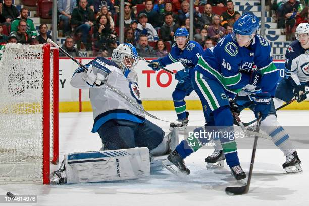 Elias Pettersson of the Vancouver Canucks takes a shot on Laurent Brossoit of the Winnipeg Jets during their NHL game at Rogers Arena December 22...