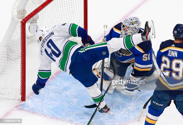 Elias Pettersson of the Vancouver Canucks trips while skating through the crease against Jordan Binnington of the St Louis Blues during the first...